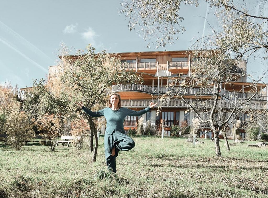 Christa Havlik mach Yogaübungen im Garten des Wellnesshotels Retter