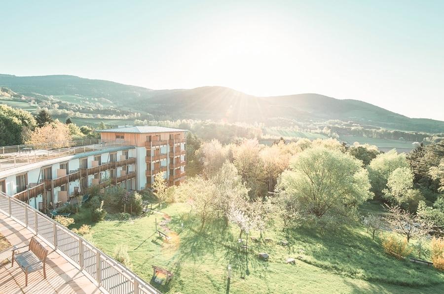 Außenansicht mit Sonne, Bäume und Hotel