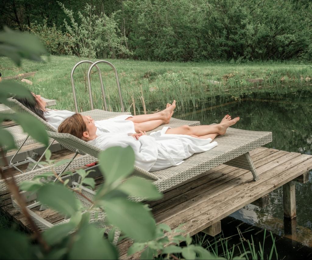 Freundinnen auf Liege beim Naturbadeteich im Wellnesshotel Retter