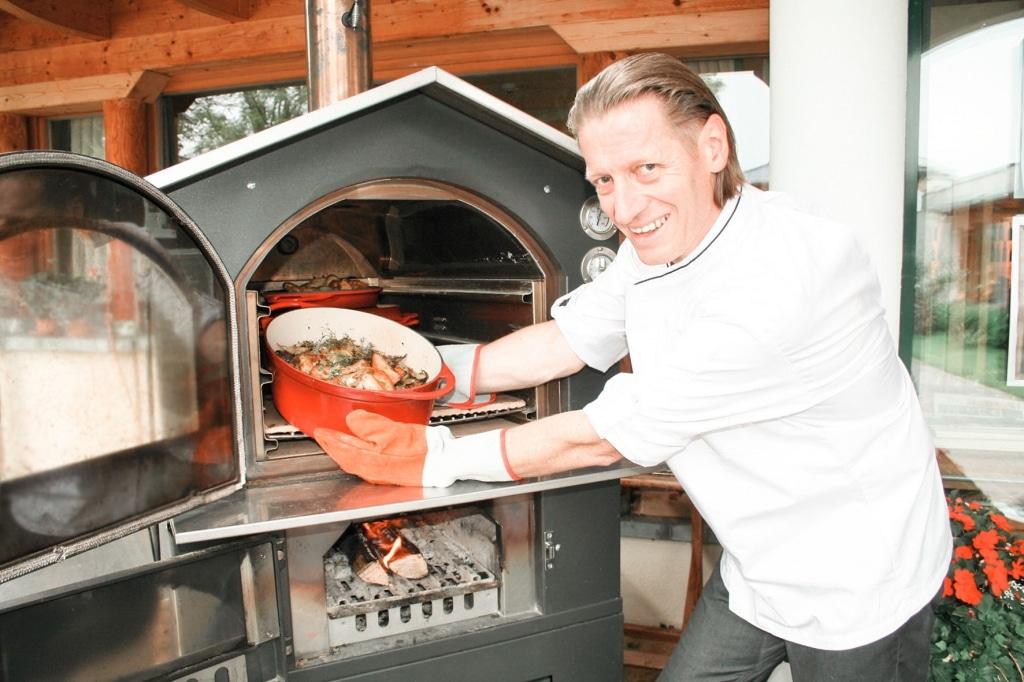 Küchenchef Jürgen Archam mit Hirschbirnhendl vor Holzsteinofen im Biohotel Retter