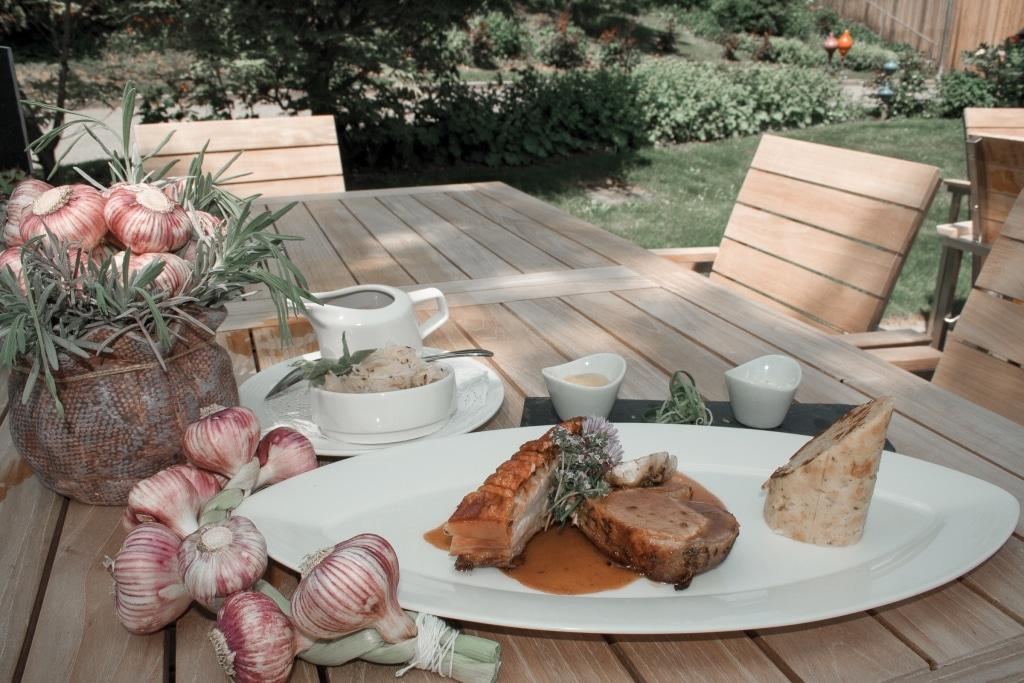 Schweinsbraten mit Serviettenknödel und Sauerkraut auf A la carte Terrasse im Biorestaurant Retter