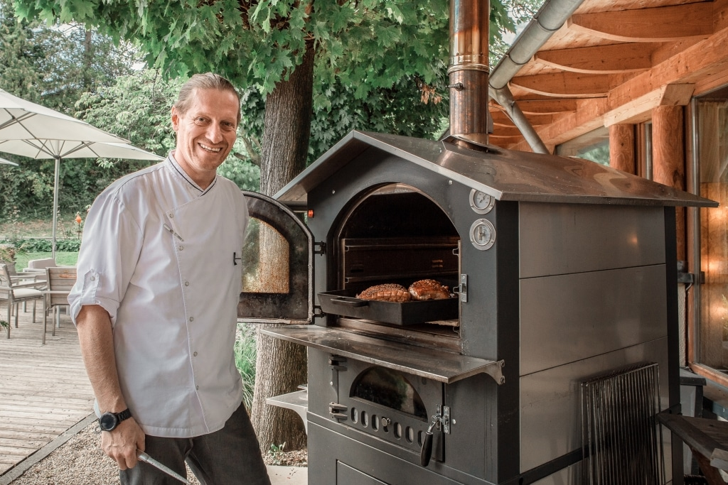 Küchenchef Jürgen Archam vor Holzhofen mit Schweinsbraten