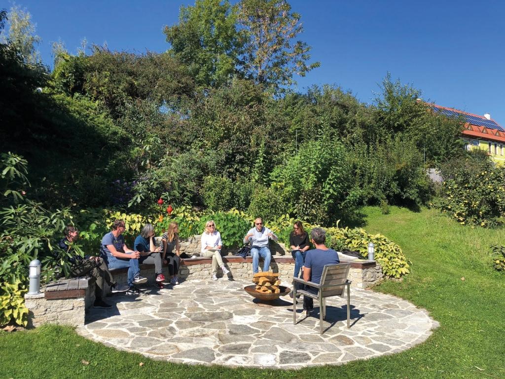 Gäste im Halbkreis bei Feuerstelle im Seminarbereich vom Biohotel Retter