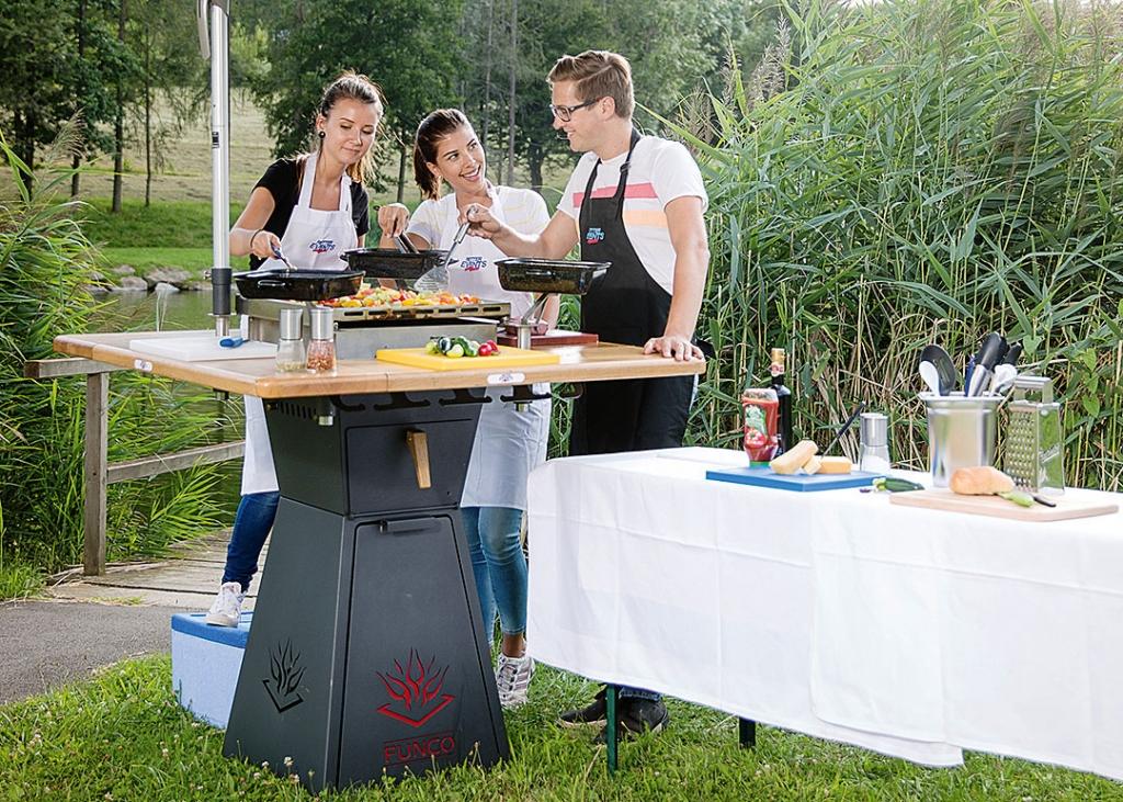 Drei Mitarbeiter von Retter Events grillen zusammen beim Rahmenprogramm Team Kochen