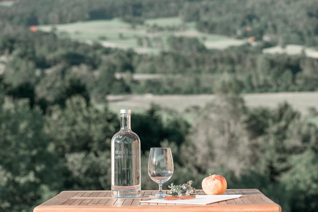 Wasserflasche mit Glas und Apfel auf Tisch