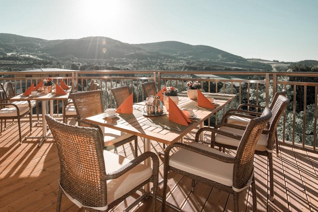 Gedeckte Tische auf Weitblickterrasse mit Sonnenuntergang im Biohotel Retter