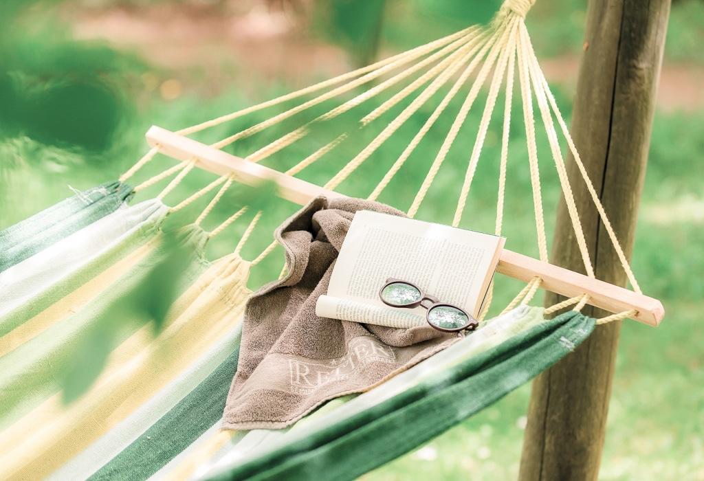 Hängematte mit Sonnenbrille, Buch und Handtuch