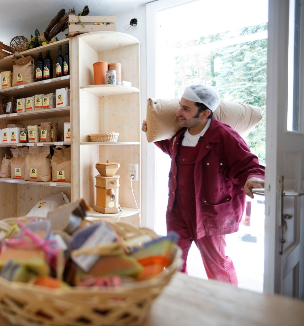 Bäcker mit Mehlsack kommt in Posch Mühle Laden herein Ausflugsziel Biohotel Retter